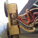 This is a true headache for any electrician aside from the numerous code violations. Your looking at the neutral side of a receptacle which has an orange and black sharing one connection screw, the wire color on this side shown should only be white..